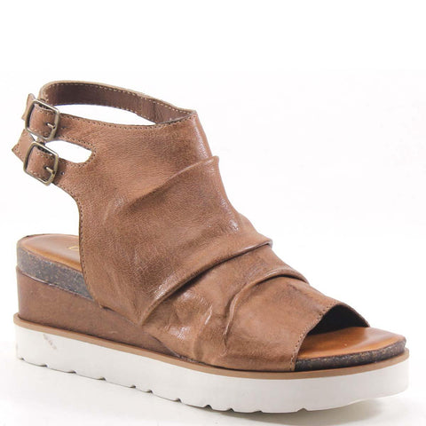 Featuring a wrapped leather ruched cuff style and double buckle closure. The open toe and back cut- out design compliments this streamlined wedge with maximum style and comfort.