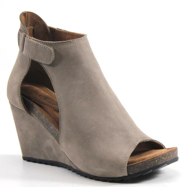 A covered wedge bootie, peep-toe design and cut out effect that wraps around the ankle with an adjustable buckle. The wrapped wedge heel meets a memory foam padded insole for superior comfort.