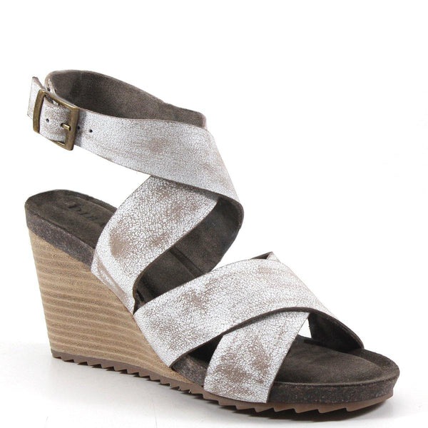 This versatile wardrobe staple has comfortable leather straps that crisscross, creating a cut-out effect that wraps around the ankle with an adjustable buckle. The stacked wedge heel meets a padded insole for maximum comfort, easily transitioning any daytime look to dinner and dancing all night long.