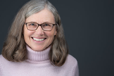 professional headshot of an older smiling women with glasses