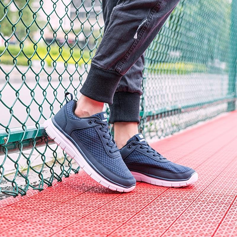 Breathable Casual Sneakers leaning on a fence