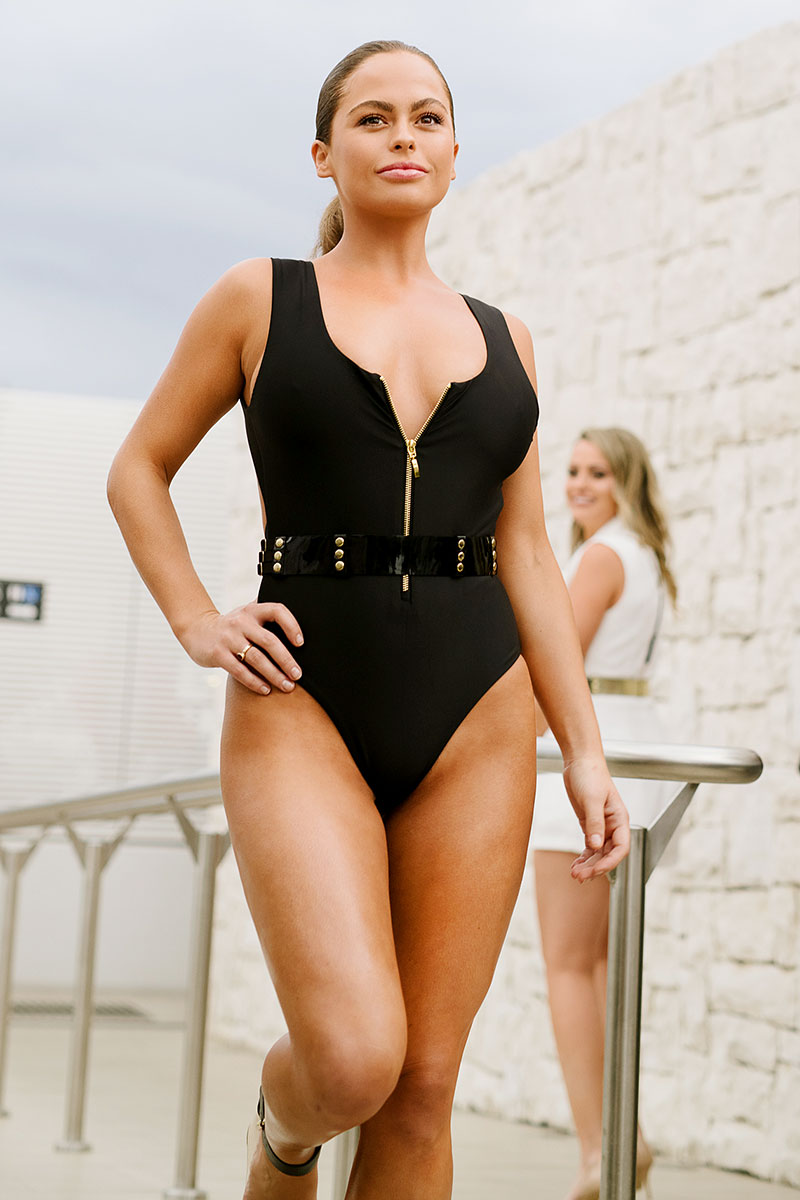 Blonde model wearing black Manda one piece swimsuit on a catwalk. Gold zipper front and full brief bottom