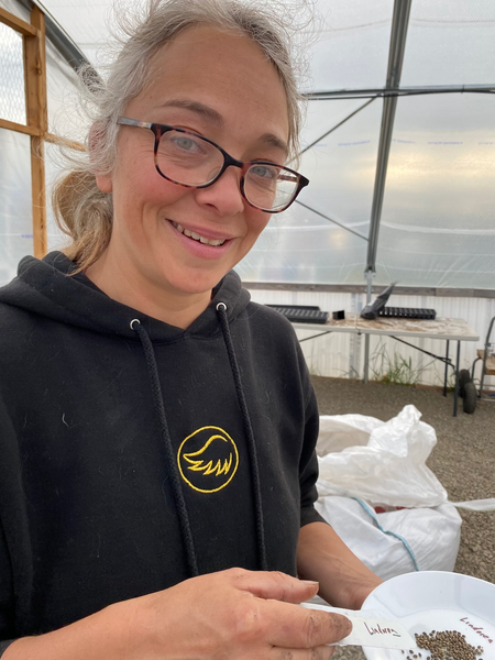 Olivia is in a black hoodie with an angel logo.  She gets ready to drop the first batch of seeds in trays in the greenhouse next to bag of soil