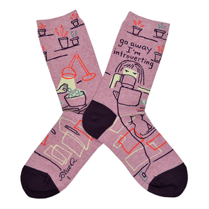 "A girl is seen at her desk eating popcorn and watching her laptop with the words ""Go away I'm introverting"" written above her on the leg of this crew length women's cotton sock by Blue Q."