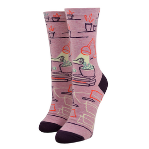 "The reverse side of this ""Go Away I'm Introverting"" Blue Q women's cotton crew socks shows a hand reaching for popcorn and miscellaneous decorations like a desk lamp and plant!"