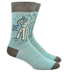 "Shown on a leg form, these light blue cotton men's crew socks with a gray heel and toe by the brand Blue Q feature a man chopping down a tree, along with the text ""Fuck This Shit""."