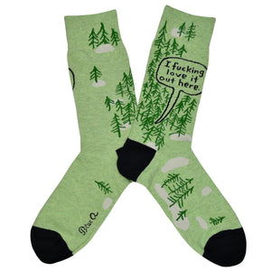 "These green cotton men's crew socks with a black heel and toe by the brand Blue Q feature simplistic trees with a large quote bubble proclaiming ""I fucking love it out here"" on the leg."