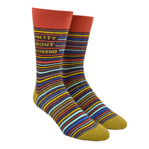 "Shown on a leg form, these blue, yellow, orange, brown and gray thinly striped men's novelty crew socks with an orange cuff by the brand Blue Q feature the words ""Pretty Decent Boyfriend"" on the leg."