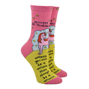 "Shown on a leg form, these pink cotton women's crew socks by the brand Blue Q feature a unicorn standing on a yellow hill in front of a blue cloud and yellow stars with the quote ""Always be yourself"" on the leg, continuing ""unless you can be a unicorn, then always be a unicorn"" written on the foot."