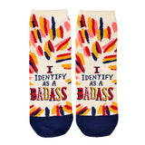 "These cream women's ankle socks with orange, pink, red and navy varied brush strokes all over them by the brand Blue Q feature the words ""I identify as a badass"" on the foot in fun, bold lettering."