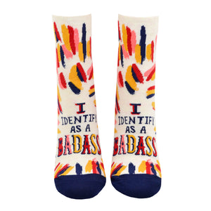 "Shown on a leg form from the front, these cream women's ankle socks with orange, pink, red and navy varied brush strokes all over them by the brand Blue Q feature the words ""I identify as a badass"" on the foot in fun, bold lettering."