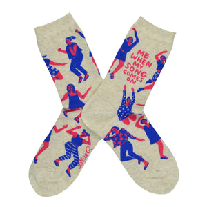 "These cream cotton women's novelty crew socks by the brand Blue Q feature pink women wearing purple clothes dancing in different styles and the quote ""Me When My Song Comes On""."