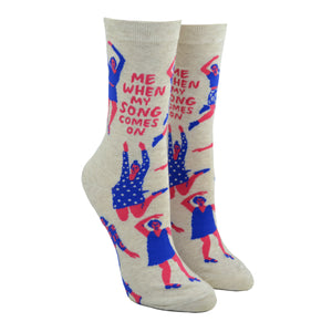 "Shown on a leg form, these cream cotton women's novelty crew socks by the brand Blue Q feature pink women wearing purple clothes dancing in different styles and the quote ""Me When My Song Comes On""."