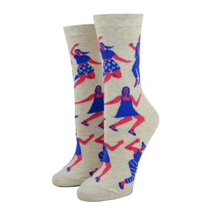 Shown on a leg form, these cream cotton women's novelty crew socks by the brand Blue Q feature pink women wearing purple clothes dancing in different styles.
