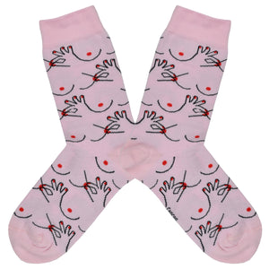 These pink cotton women's crew socks by the brand Coucou Suzette feature bare breasts and a hand pinching one of the nipples.