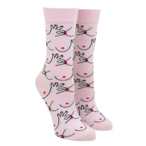 Shown on a leg form, these pink cotton women's crew socks by the brand Coucou Suzette feature bare breasts and a hand pinching one of the nipples.