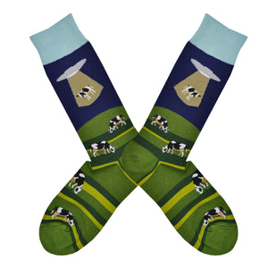 These blue and green cotton men's crew socks with a light blue cuff by the brand Foot Traffic feature an alien spaceship beaming up a cow that was grazing in a field.
