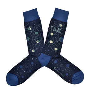 "These blue cotton men's crew socks by the brand Foot Traffic feature small blue outlines of the planets on the leg and foot and rings around earth with the moon revolving in all its phases. The words ""It's just a phase"" are written at the top of the sock."