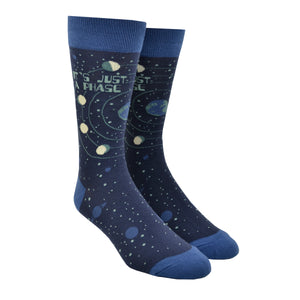"Shown on a leg form, these blue cotton men's crew socks by the brand Foot Traffic feature small blue outlines of the planets on the leg and foot and rings around earth with the moon revolving in all its phases. The words ""It's just a phase"" are written at the top of the sock."