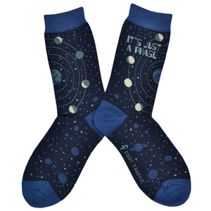 "These blue cotton women's crew socks by the brand Foot Traffic feature small blue outlines of the planets  on the leg and foot and rings around the earth with the moon revolving in all its phases. The words ""It's just a phase"" are written at the top of the sock."