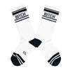"These white cotton unisex crew socks with a black toe and striped cuff by the brand Gumball Poodle feature the words ""BITCH"" on the leg."