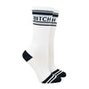 "Shown on a leg form, these white cotton unisex crew socks with a black toe and striped cuff by the brand Gumball Poodle feature the words ""BITCH"" on the leg."