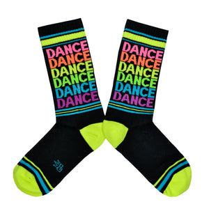 These black cotton American Made unisex crew socks with a neon green and blue striped heel and toe by the brand Gumball Poodle feature the word dance repeated in fun neon colors down the leg.