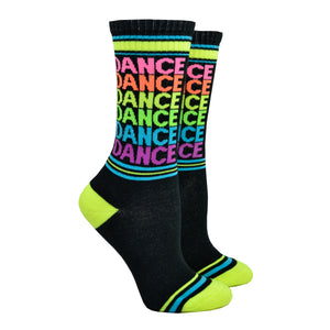 Shown on a leg form, these black cotton American Made unisex crew socks with a neon green and blue striped heel and toe by the brand Gumball Poodle feature the word dance repeated in fun neon colors down the leg.