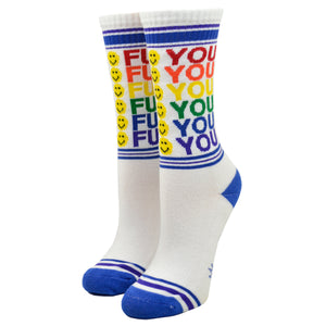 "Shown on a leg form, these white cotton unisex crew socks with a blue toe and striped cuff by the brand Gumball Poodle feature the words ""FUCK YOU"" in rainbow colors repeated down the leg and emoji smiley faces running down the front."