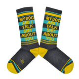 "These gray cotton unisex crew socks with a yellow toe and yellow and blue striped cuff by the brand Gumball Poodle feature the words ""MY DOG AND I TALK SHIT ABOUT YOU"" on the leg."