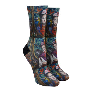 Shown on a leg form, these beautiful women's crew socks by the brand Good Luck Socks feature an iconic self portrait of the artist Frida Kahlo with a monkey and a parrot on each shoulder, roses in her hair and a realistic beating red heart on her chest, depicted with many vivid beautiful colors.
