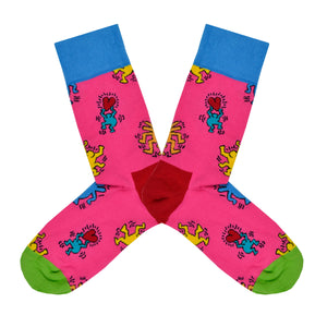 These pink cotton women's crew socks with a green toe, red heel and blue cuff by the brand Happy Socks feature the artwork of Keith Haring showing simple outlines of blue and yellow people dancing and holding red hearts.