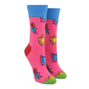 Shown on a leg form, these pink cotton women's crew socks with a green toe, red heel and blue cuff by the brand Happy Socks feature the artwork of Keith Haring showing simple outlines of blue and yellow people dancing and holding red hearts.