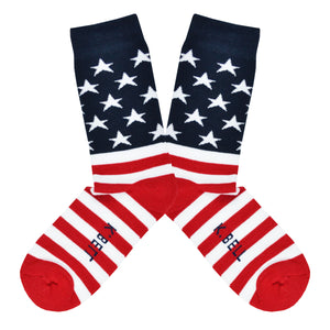 These iconic men's cotton crew socks by the brand K. Bell celebrate the flag of the United States of American, showcasing red and white stripes on the foot, and a navy blue background with white stars on the leg.