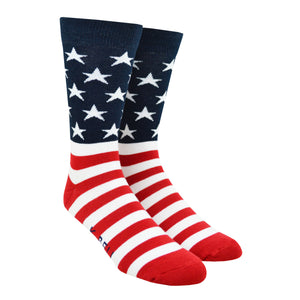 Shown on a leg form, these iconic men's cotton crew socks by the brand K. Bell celebrate the flag of the United States of American, showcasing red and white stripes on the foot, and a navy blue background with white stars on the leg.
