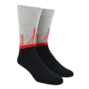 Shown on a leg form, these cool men's cotton crew socks by the brand K. Belll feature a simple design with a black foot and gray leg, separated by the sleek red arches of the San Francisco landmark the Golden Gate Bridge, viewed as if you were moving down it.