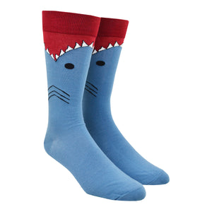 Shown on a leg form, these blue cotton men's novelty crew socks with a red top and cuff by the brand K Bell make it look like a shark is eating your leg, showing the sharks gills, eyes and teeth chomping on your calf.