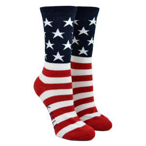 Shown on a leg form, these iconic women's cotton crew socks by the brand K. Bell celebrate the flag of the United States of American, showcasing red and white stripes on the foot, and a navy blue background with white stars on the leg.