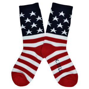 These iconic women's cotton crew socks by the brand K. Bell celebrate the flag of the United States of American, showcasing red and white stripes on the foot, and a navy blue background with white stars on the leg.