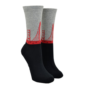 Shown on a leg form, these cool women's cotton crew socks by the brand K. Belll feature a simple design with a black foot and gray leg, separated by the sleek red arches of the San Francisco landmark the Golden Gate Bridge, viewed as if you were moving down it.