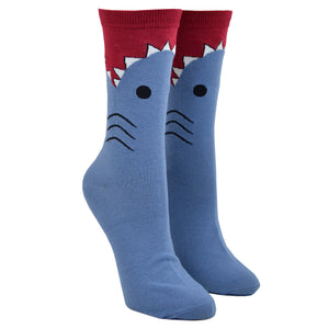 Shown on a leg form, these blue cotton women's novelty crew socks with a red top and cuff by the brand K Bell make it look like a shark is eating your leg, showing the sharks gills, eyes and teeth chomping on your calf.