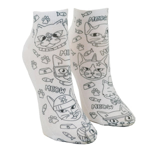 Shown on a leg form, these fun white cotton socks with different silly cats on them come with Crayola fabric markets in purple, blue, pink and yellow to color in your own unique design.