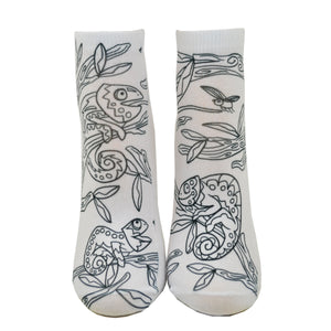 Shown from the front on a leg form, these fun white cotton socks with different chameleons sitting in a tree on them come with Crayola fabric markets in red, orange, green and blue to color in your own unique design.