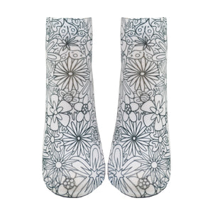 Shown from the front on a leg form, these white cotton socks with a beautiful floral design on them come with Crayola fabric markets in pastel purple, blue, pink and yellow to color in your own unique design.