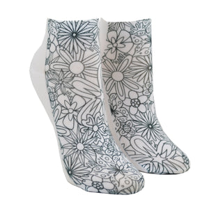 Shown on a leg form, these white cotton socks with a beautiful floral design on them come with Crayola fabric markets in pastel purple, blue, pink and yellow to color in your own unique design.