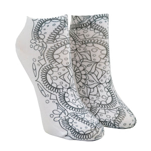 Shown on a leg form, these white cotton socks with a beautiful mandala design on them come with Crayola fabric markets in pastel purple, blue, pink and yellow to color in your own unique design.
