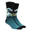 Shown on a leg form, these black and blue bamboo men's crew socks by the brand Socksmith are based on the famous print The Great Wave by the Japanese artist Hokusai.