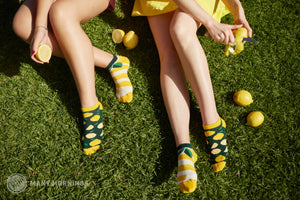 Two people sit on grass peeling lemons while wearing a mismatched pair of Many Morning's unisex cotton ankle socks that show lemons on sock and a big lemon peel on the other sock.