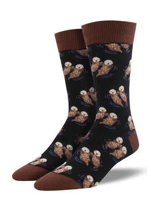 Shown on a leg form, these black cotton men's crew socks with a brown heel, toe and cuff by the brand Socksmith feature adorable otters floating in the ocean holding hands.