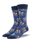 Shown on a leg form, these blue cotton men's crew socks with a navy heel, toe and cuff by the brand Socksmith feature adorable otters floating in the ocean holding hands.